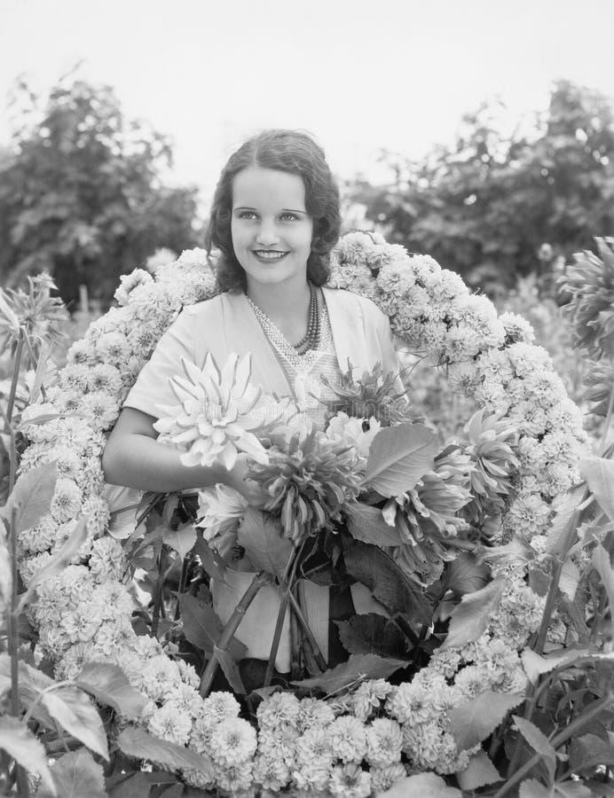 Mujer joven que se sienta en jardín en una guirnalda de flores (todas las personas representadas no son vivas más largo y ningún  imagen de archivo