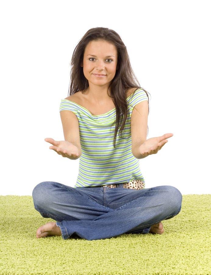 Mujer joven que se sienta en la alfombra verde fotografía de archivo libre de regalías