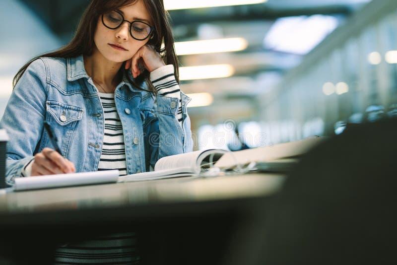 Mujer joven que se sienta en la biblioteca y estudiar de universidad Notas de la escritura de la muchacha en el campus de la univ imagen de archivo libre de regalías