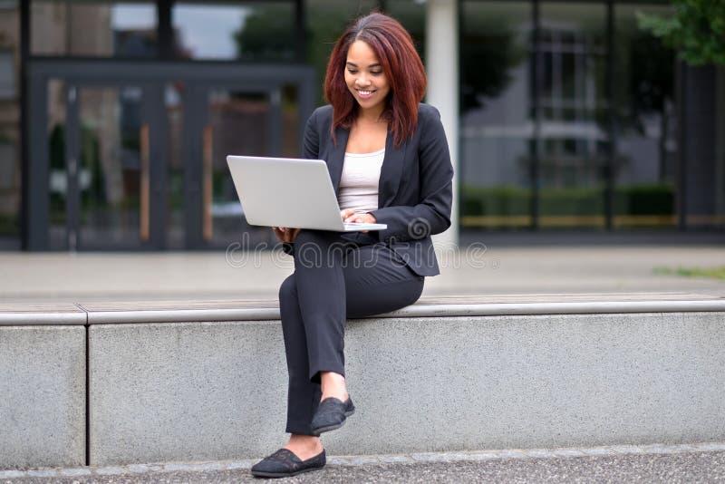 Mujer joven que se sienta en la ciudad que trabaja en un ordenador portátil fotos de archivo libres de regalías