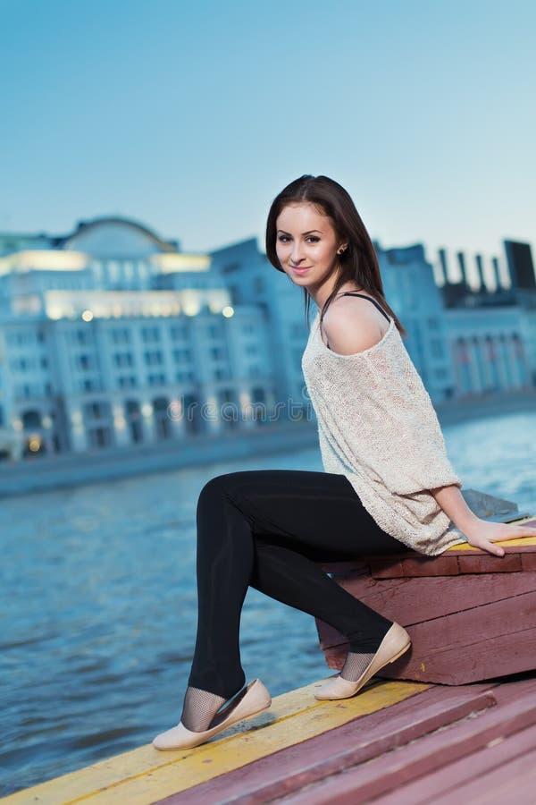 Mujer joven que se sienta en la costa por el agua foto de archivo libre de regalías