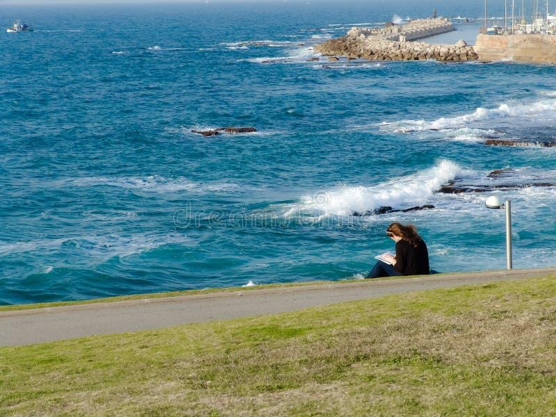 Mujer joven que se sienta en la hierba verde en el parque, lectura, supervisando una vista del océano y del puerto de Jaffa fotografía de archivo libre de regalías