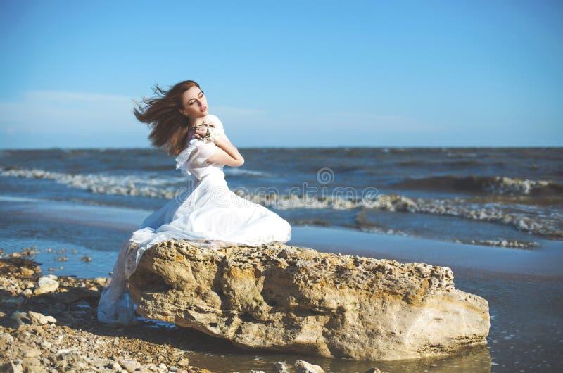 mujer joven que se sienta en la piedra en la costa de mar fotografía de archivo libre de regalías