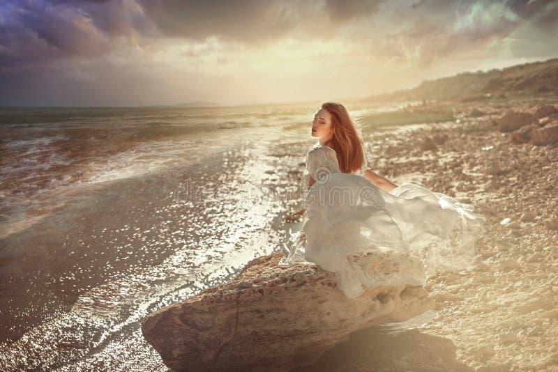 mujer joven que se sienta en la piedra en la costa de mar fotos de archivo libres de regalías