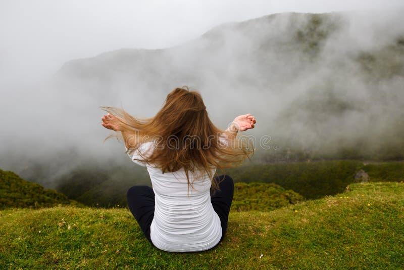Mujer joven que se sienta en la posición de loto en las montañas foto de archivo