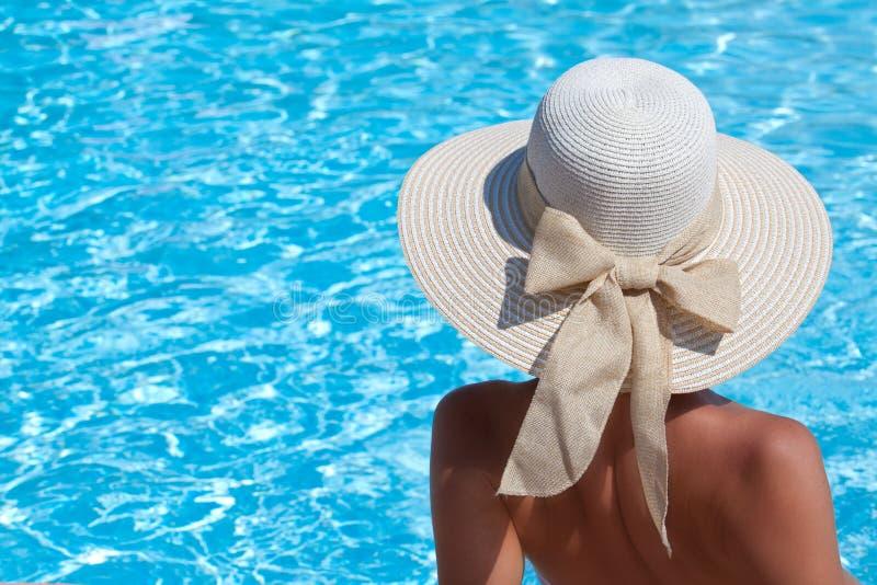 Mujer joven que se sienta en la repisa de la piscina fotos de archivo libres de regalías