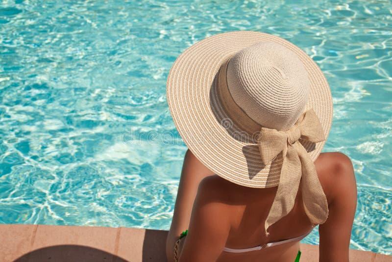 Mujer joven que se sienta en la repisa de la piscina foto de archivo
