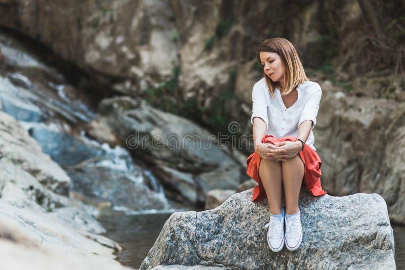 Mujer joven que se sienta en la roca por el río imagenes de archivo