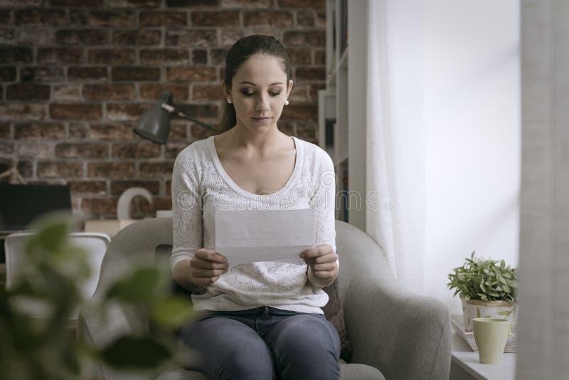 Mujer joven que se sienta en la sala de estar y que lee una letra foto de archivo