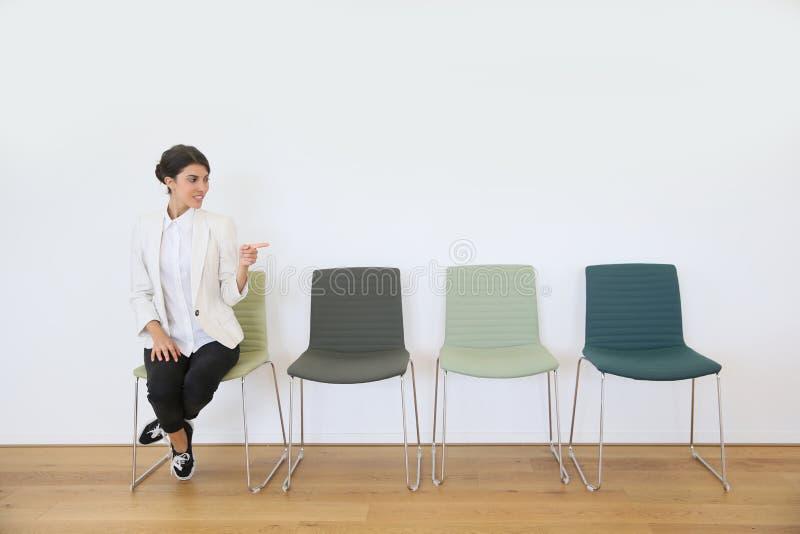 Mujer joven que se sienta en la silla que señala el finger foto de archivo
