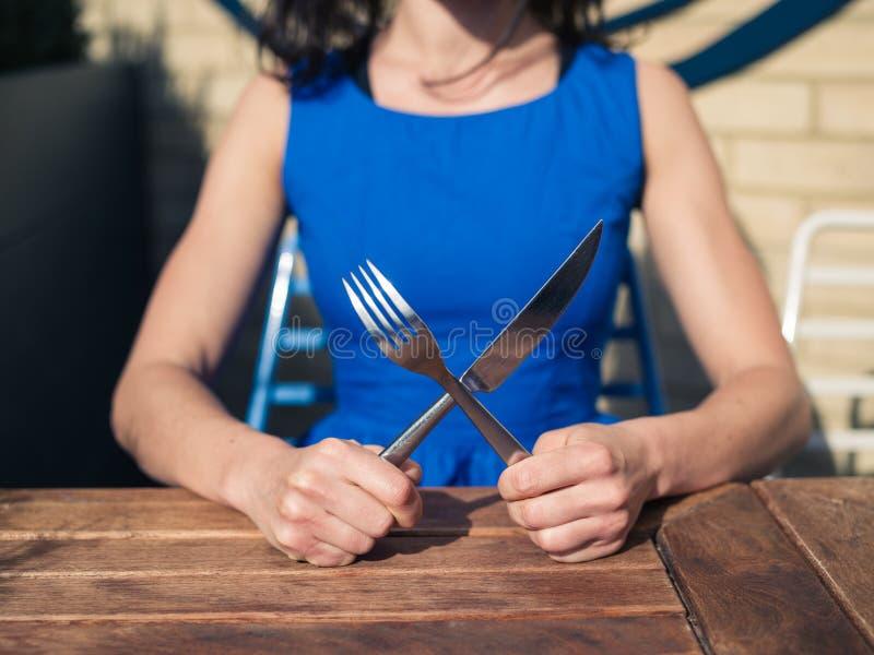 Mujer joven que se sienta en la tabla con la bifurcación y el cuchillo imagen de archivo libre de regalías