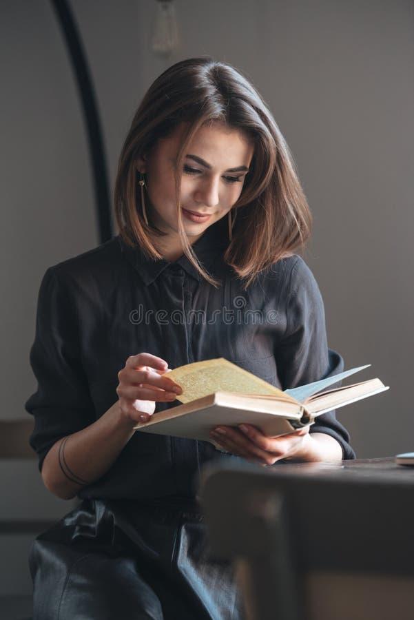 Mujer joven que se sienta en la tabla en café y libro de lectura foto de archivo libre de regalías