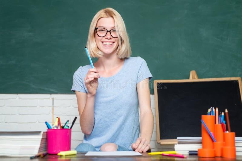 Mujer joven que se sienta en la tabla que hace la biblioteca de las asignaciones Retrato del estudiante universitario en universi imagen de archivo libre de regalías