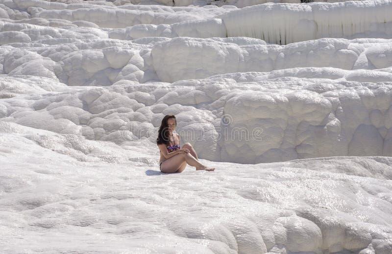 Mujer joven que se sienta en los travertinos en Pamukkale foto de archivo