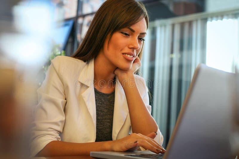 Mujer joven que se sienta en oficina y que trabaja en el ordenador portátil imagenes de archivo