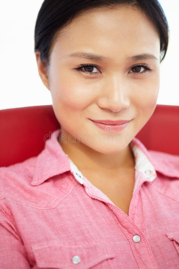 Mujer joven que se sienta en silla imagen de archivo
