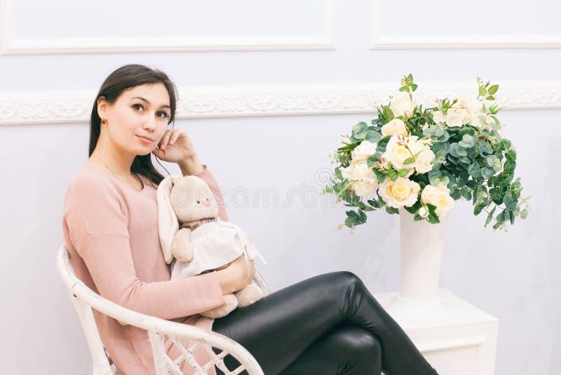 Mujer joven que se sienta en silla de mimbre en casa fotografía de archivo