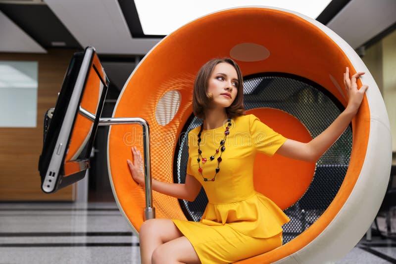 Mujer joven que se sienta en silla del ordenador fotografía de archivo