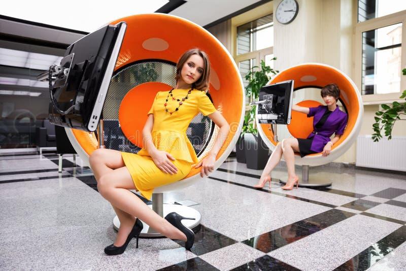 Mujer joven que se sienta en silla del ordenador en oficina fotos de archivo