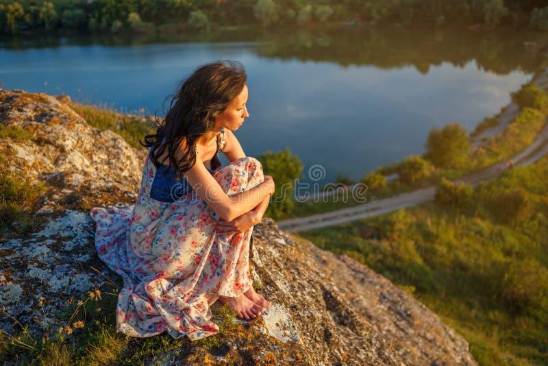 Mujer joven que se sienta en un acantilado que pasa por alto el lago, humor triste, por la tarde en la puesta del sol imágenes de archivo libres de regalías