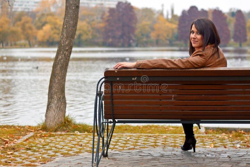 Mujer joven que se sienta en un banco en el parque imagenes de archivo