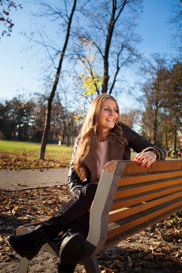 Mujer joven que se sienta en un banco en el parque de la ciudad en otoño/invierno imagen de archivo libre de regalías