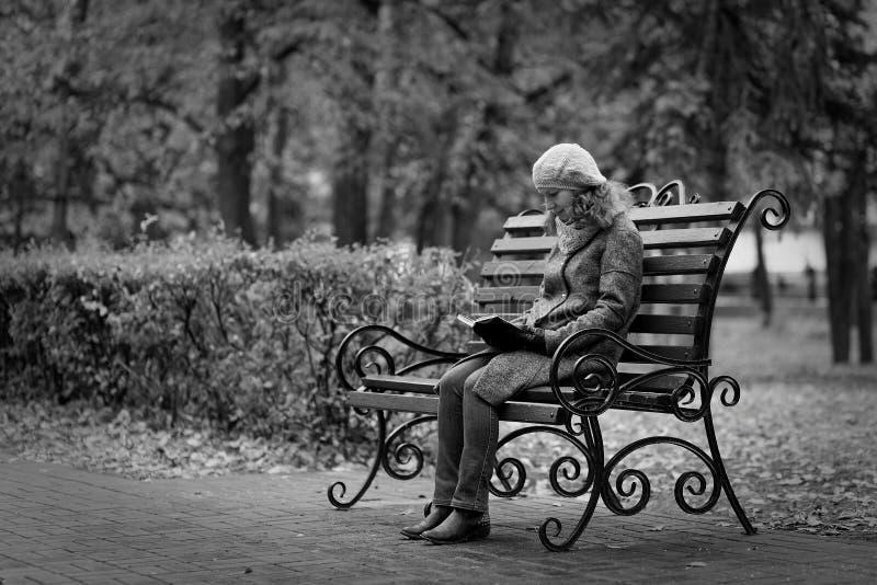 Mujer joven que se sienta en un banco y que lee un libro foto de archivo