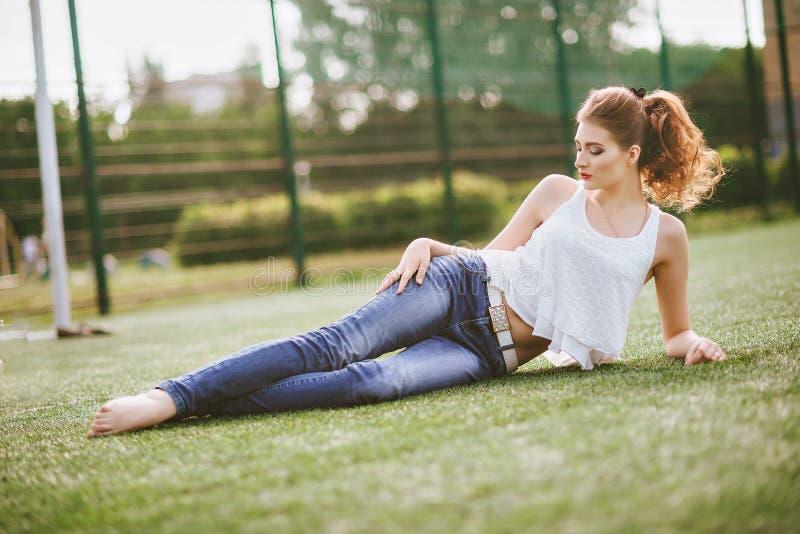 Mujer joven que se sienta en un campo de fútbol verde, vestido en tejanos, una camiseta blanca Labios rojos foto de archivo