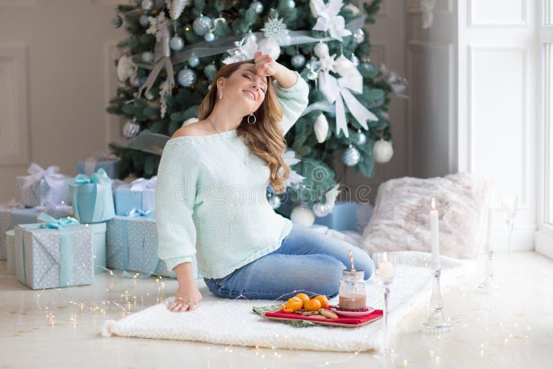 Mujer joven que se sienta en un cuarto con un árbol de navidad y las cajas de regalo en el fondo Mujeres rubias que sonríen y que fotos de archivo libres de regalías