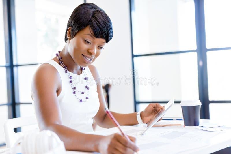 Mujer joven que se sienta en un escritorio en una oficina y que trabaja en modelo fotografía de archivo libre de regalías