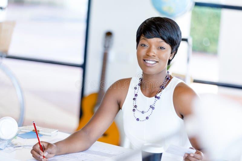 Mujer joven que se sienta en un escritorio en una oficina y que trabaja en modelo fotos de archivo