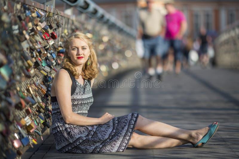 Mujer joven que se sienta en un puente peatonal, el puente del amor con las broches fotos de archivo