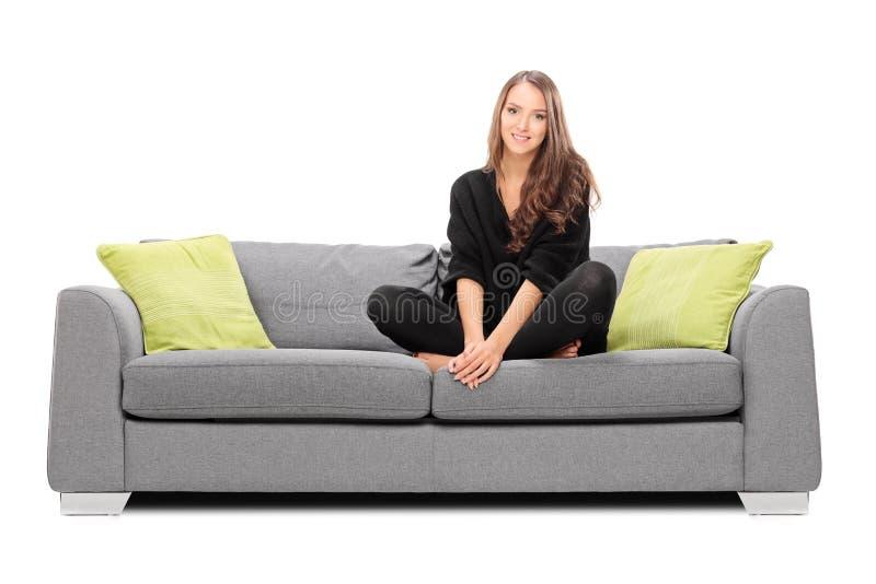 Mujer joven que se sienta en un sofá y que mira en la cámara fotos de archivo