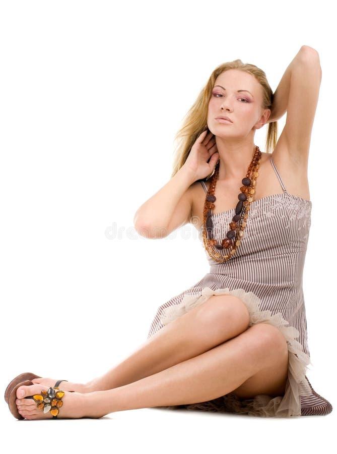 Mujer joven que se sienta en un suelo fotos de archivo