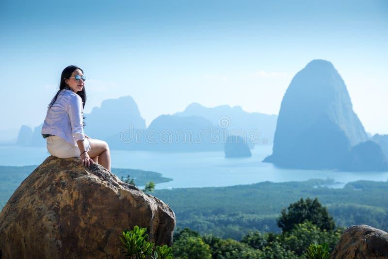 Mujer joven que se sienta en un top de la montaña foto de archivo