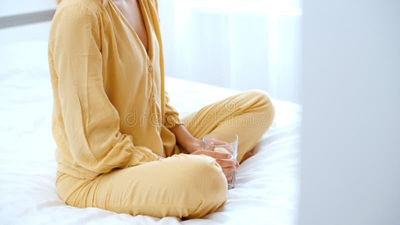 Mujer joven que se sienta en una cama y un agua potable imágenes de archivo libres de regalías