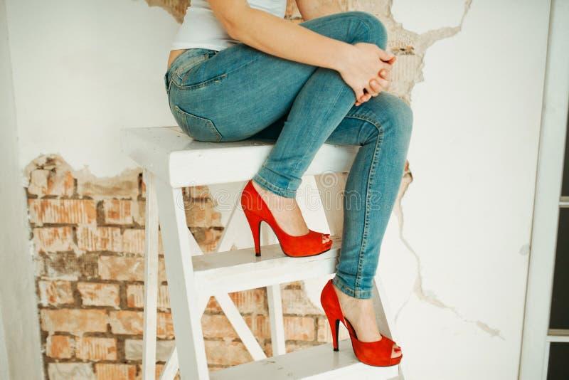 Mujer joven que se sienta en una escalera de mano imagen de archivo