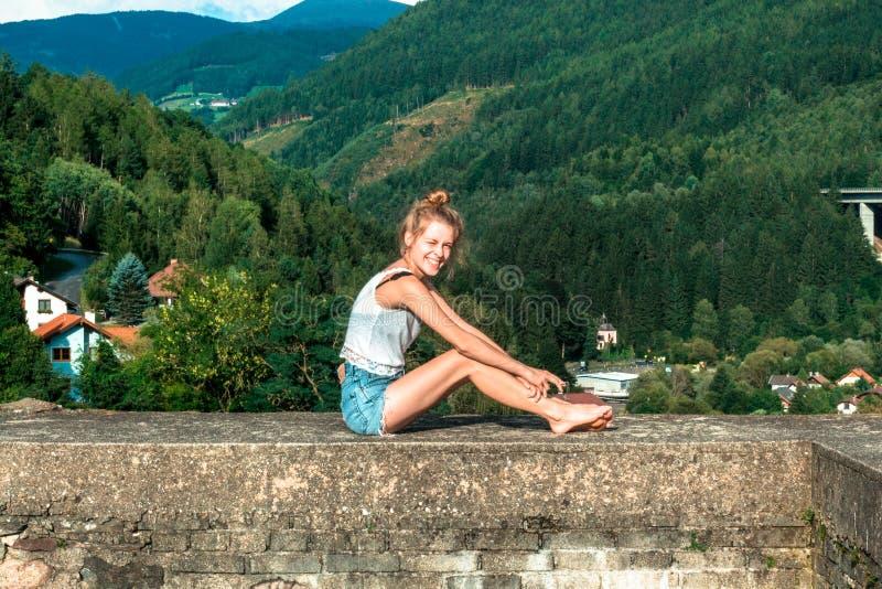 Mujer joven que se sienta en una pared de piedra en bosque fotografía de archivo libre de regalías