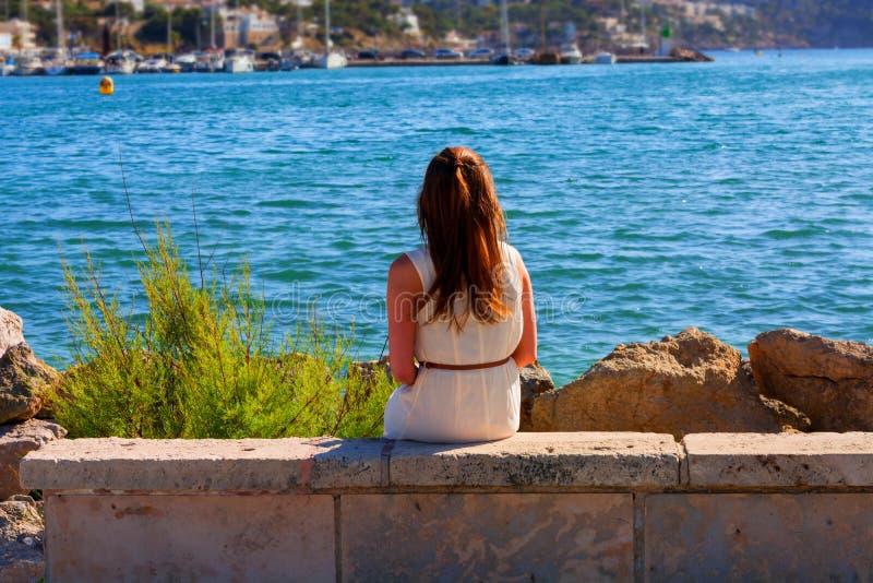 Mujer joven que se sienta en una pared en puerto fotografía de archivo libre de regalías