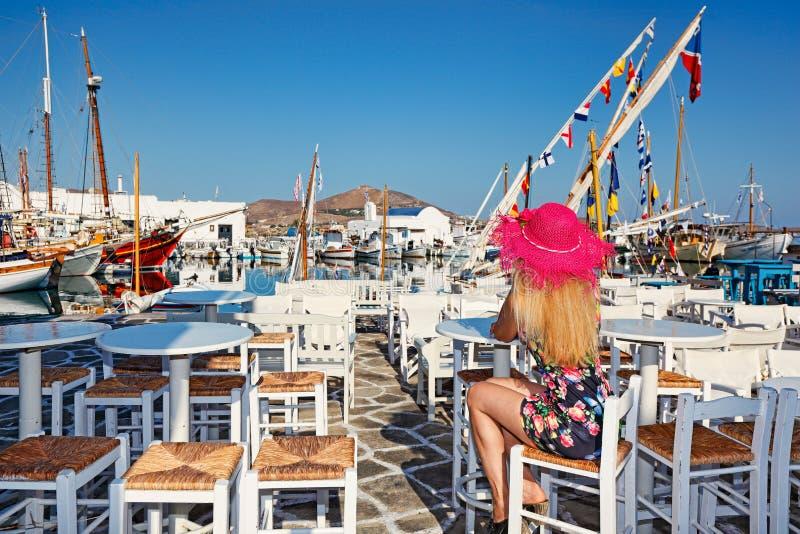 Mujer joven que se sienta en una taberna tradicional en Naousa de Paros, Grecia foto de archivo libre de regalías