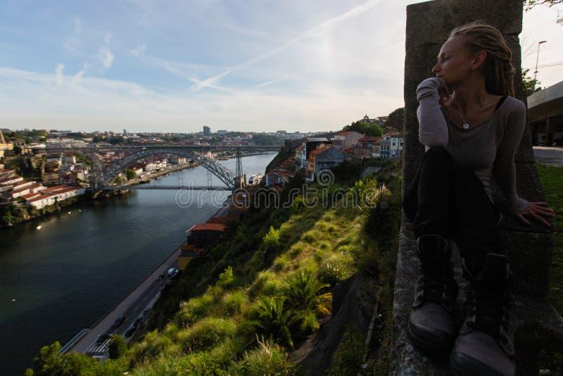 Mujer joven que se sienta enfrente del puente de Dom Luis I en el río del Duero, Oporto imagenes de archivo