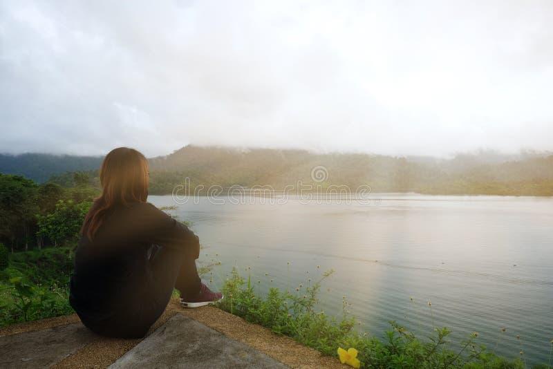 Mujer joven que se sienta solamente en el acantilado el frente de ella tiene el mar y su fotos de archivo