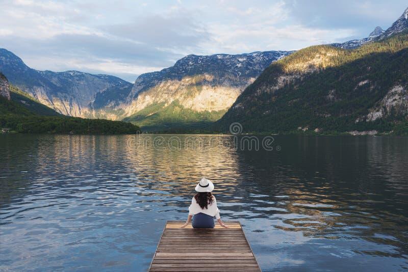 Mujer joven que se sienta solamente en el embarcadero de madera, mirando el lago y el Mountain View en verano Hallstatt, Austria imagenes de archivo