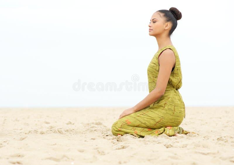 Mujer joven que se sienta solamente y que medita en la playa imagen de archivo