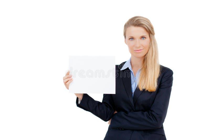 Mujer joven que se sostiene en la tarjeta en blanco en su mano imagenes de archivo
