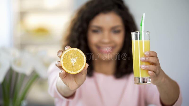 Mujer joven que se sostiene hacia fuera anaranjada y vidrio de jugo y que sonríe, rico en vitaminas fotografía de archivo libre de regalías