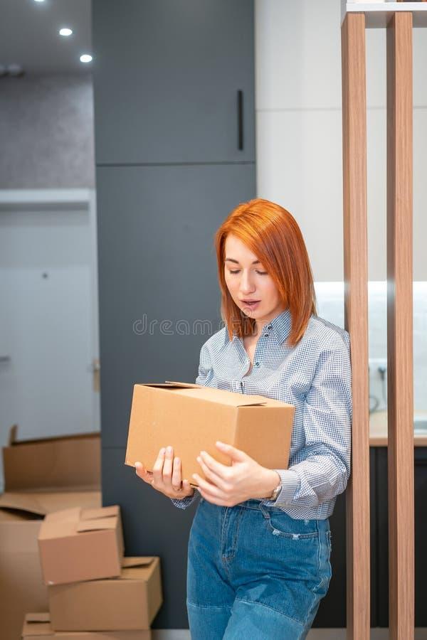 Mujer joven que se traslada al nuevo apartamento que sostiene las cajas de cartón imagenes de archivo