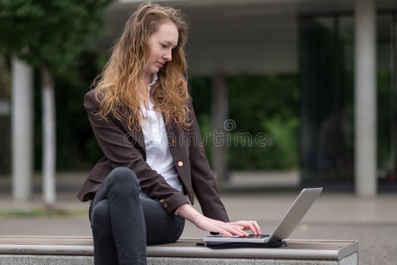 Mujer joven que sienta al aire libre el trabajo en un ordenador portátil imágenes de archivo libres de regalías