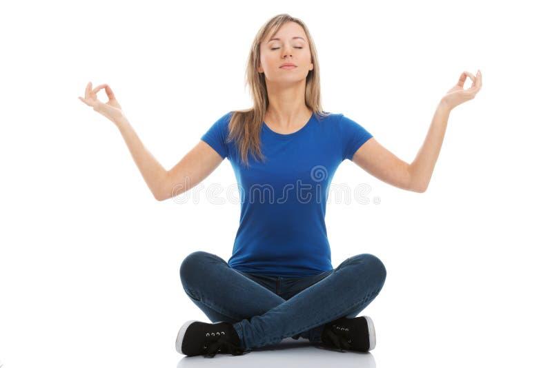 Mujer joven que sienta y que hace yoga. foto de archivo libre de regalías
