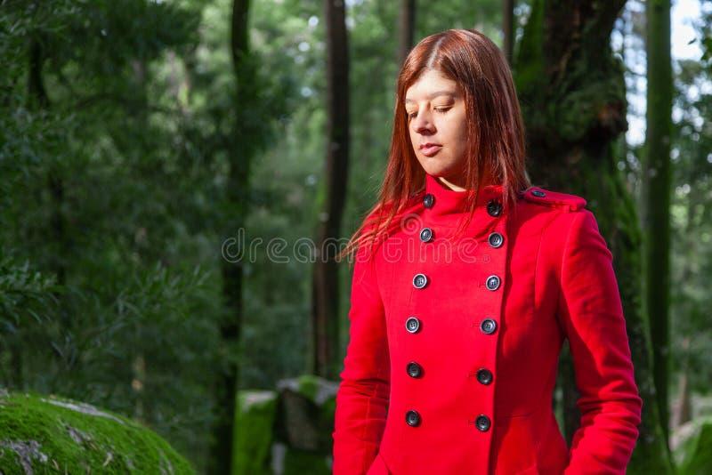 Mujer joven que siente caminar triste solamente en la trayectoria de bosque que lleva la capa larga roja foto de archivo